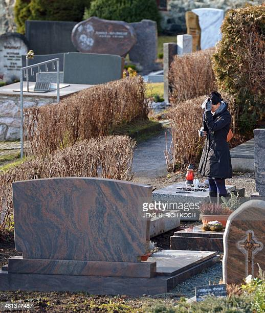 A woman stands in front of a grave that was opened on January 8 2014 in connection with the case of a girl missed since the year 2001 at the cemetery...