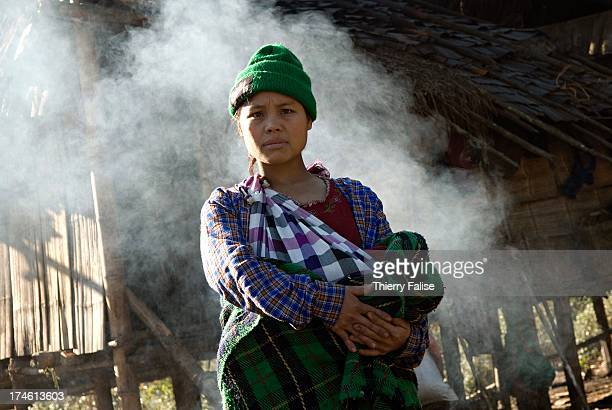 A woman stands in front of a hut made from leaves branches and plastic sheets in the jungle of the Northern Karen State where she lives after being...