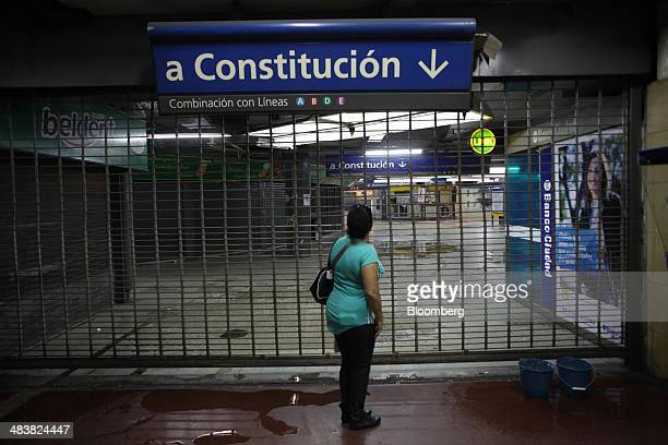 A woman stands in front of a metal gate blocking the entrance to the Retiro Subway Station in Buenos Aires Argentina on Thursday April 10 2014...