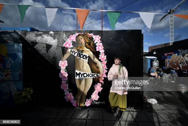 A woman stands in front of a mural supporting the Yes vote located inside the Bernard Shaw pub on May 13 2018 in Dublin Ireland The referendum on the...