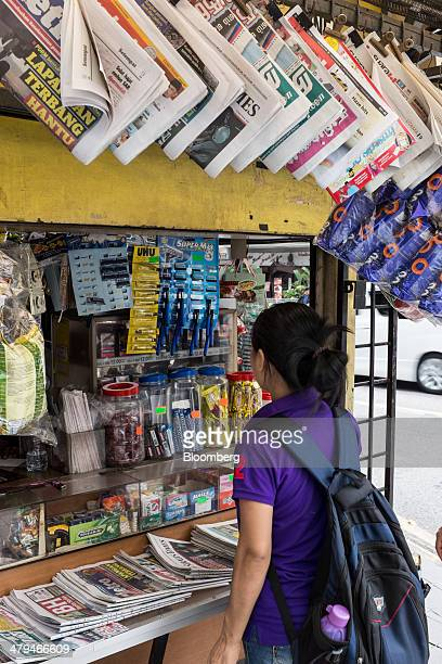 Woman stands in front of a news stand in Kuala Lumpur, Malaysia, on Tuesday, March 18, 2014. Malaysia, aspiring to become a developed nation in six...