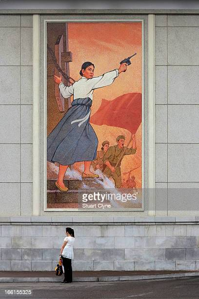 CONTENT] A woman stands in front of a propaganda poster showing a woman with a gun and soldiers carrying a flag