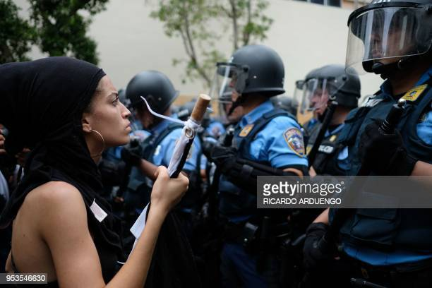 A woman stands in front of a riot police line during a May Day protest against pension cuts school closures and slow hurricane recovery efforts in...