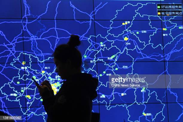 Woman stands in front of a screen displaying service network based on the Chongqing New Type Internet of Things Big Data Service Platform for Digital...