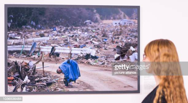 A woman stands in front of a tsunami picture by photographer Arita Tsutomu at the exhibition 'Von Atlantis bis heute Mensch Natur Katastrophe' in...