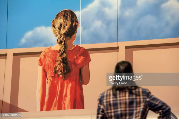 A woman stands in front of a wall painting at the 50th World Economic Forum in Davos