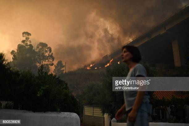 A woman stands in front of a wildfire burning near the highway A23 following a new rash of forest fires ahead of a weekend of warm temperatures at...