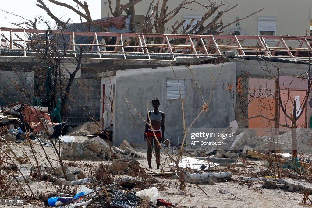 TOPSHOT - A woman stands in front of a wrecked house days after this Caribbean island sustained extensive damage in the wake of Hurricane Irma, Friday, September 15, 2017 in St. Martin. / AFP PHOTO / Ricardo ARDUENGO