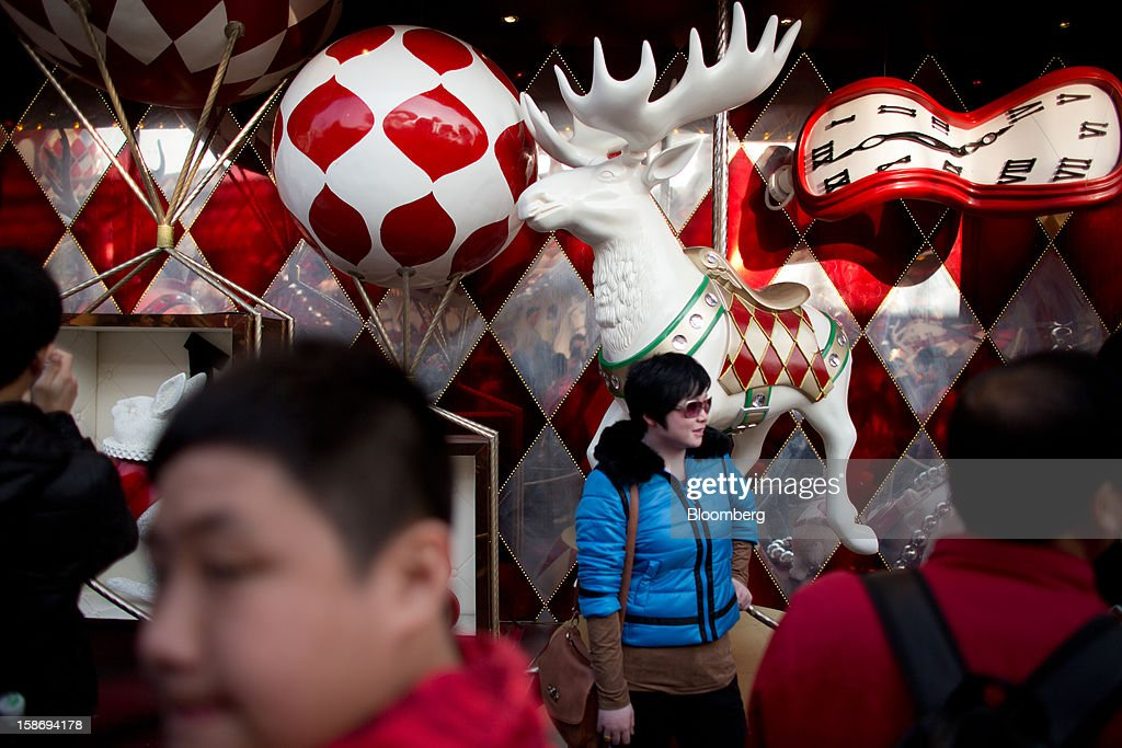 A woman stands in front of Christmas decorations outside a shopping mall in the Tsim Sha Tsui area of Hong Kong, China, on Saturday, Dec. 22, 2012. Hong Kong's economy is set for its weakest annual expansion since the global financial crisis as the European sovereign debt crisis damps global trade. Photographer: Lam Yik Fei/Bloomberg via Getty Images
