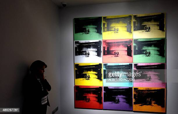 A woman stands in front of 'Electric Chairs' paintings by US artist Andy Warhol as part of the exhibition 'Warhol' on April 17 2014 in Rome The works...