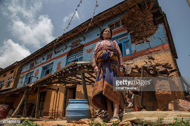 A woman stands in front of her damaged home on May 1 2015 in Kalchowk Nepal A major 78 earthquake hit Kathmandu midday on Saturday and was followed...