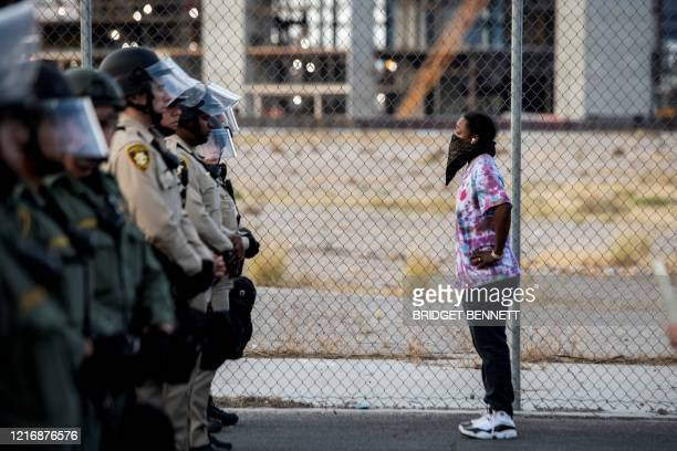 TOPSHOT A woman stands in front of Police officers on June 1 in downtown Las Vegas as they take part in a Black lives matter rally in response to the...