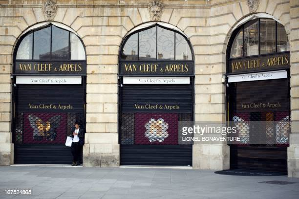 A woman stands in front of shop windows of a closed Van Cleef Arpels jewellery store on April 26 2013 at the Place Vendome in Paris AFP PHOTO /...