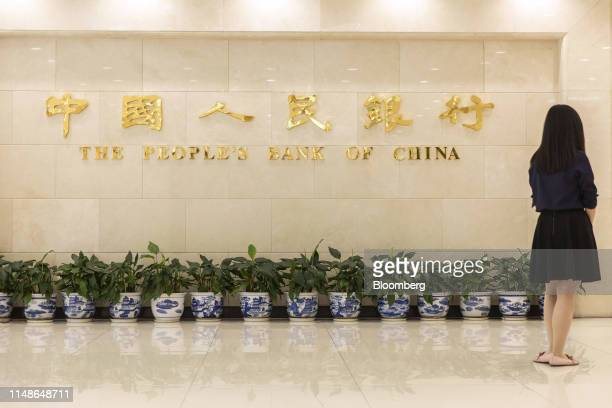 Woman stands in front of signage at the lobby of the People's Bank of China headquarters in Beijing, China, on Friday, June 7, 2019. China's central...