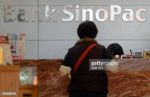 A woman stands in front of the counter at the Bank of SinoPac in Taipei on April 3 2013 Share prices on Taiwan's SinoPac Financial Holdings rose 28...