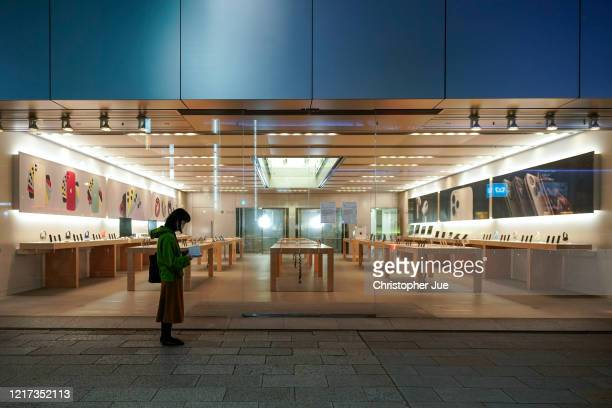Woman stands in front of the entrance of an empty Apple store as it has been temporarily closed for the time being in Tokyo's upscale Ginza district...