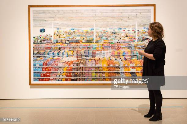 A woman stands in front of the image entitled '99 Cent' by Andreas Gursky in the reopened Hayward Gallery on January 24 2018 in London England