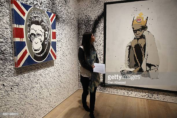 Woman stands in front of two pieces of work entitled 'Burger King Kid' and Monkey Queen during a press preview of the first unauthorized...