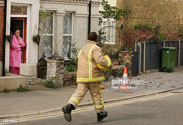 Woman stands in her front door and uses a mobile phone after an earthquake caused damage to her chimney on April 28, 2007 in Folkstone, Kent. The...