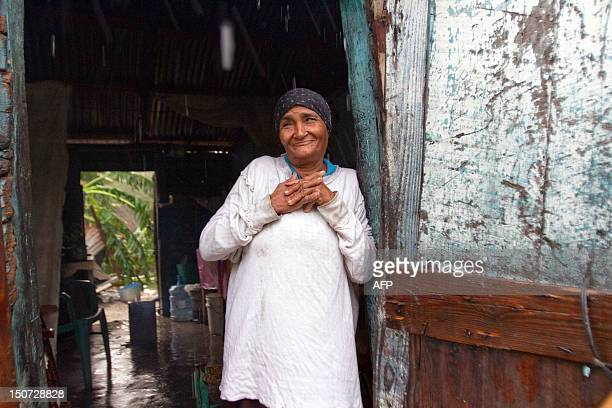 A woman stands in her house after the passage of Tropical Storm Isaac in Barahona southwestern Dominican Republic on August 25 2012 Tropical Storm...