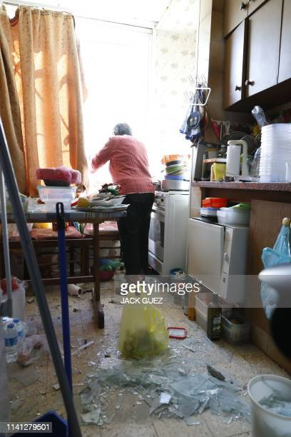 A woman stands in her kitchen that was damaged by a rocket strike on the southern Israeli city of Ashkelon near the Gaza border on May 5 2019 Gaza...