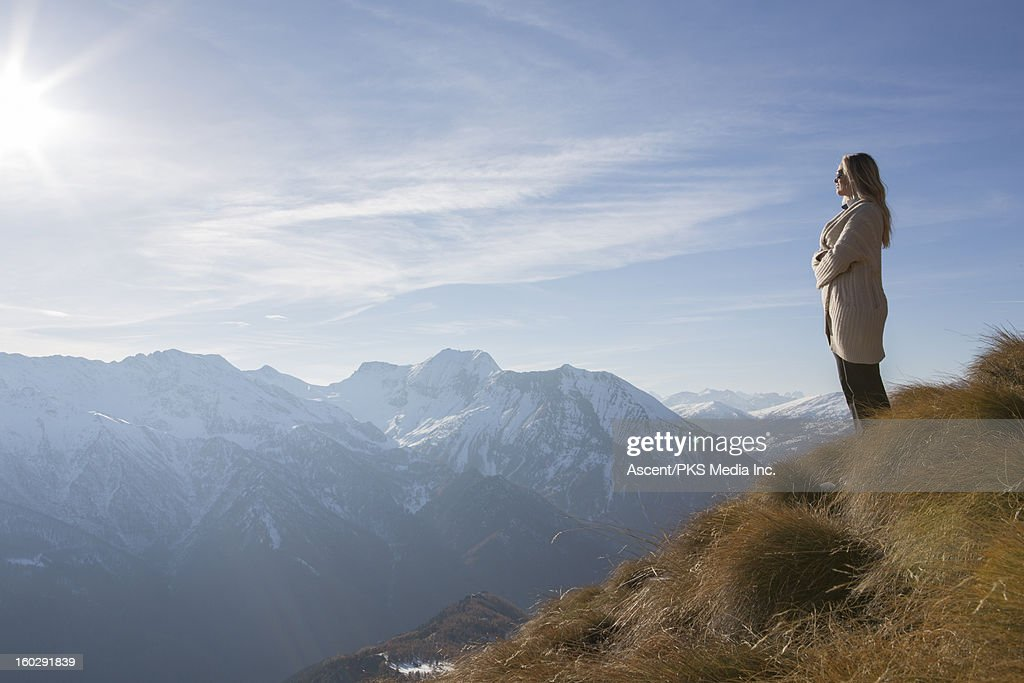 Woman stands in high mountain meadow, looking out : Stock Photo