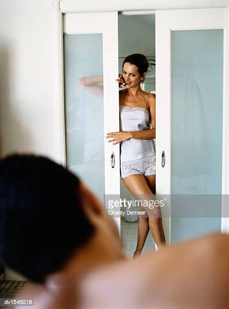woman stands in lingerie at a bathroom door flirting with a man lying on a bed - woman open legs stock photos and pictures