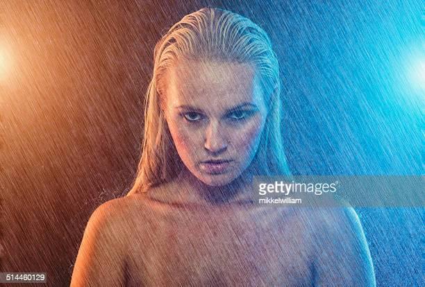 Mujer está en la lluvia en la noche