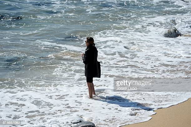 A woman stands in the sea on a beach of Badalona near Barcelona on March 10 2016 / AFP / JOSEP LAGO