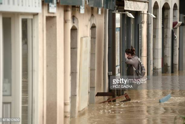 A woman stands in thighhigh flood waters looking into a shop window following heavy rains in SaliesdeBearn south western France on June 13 2018