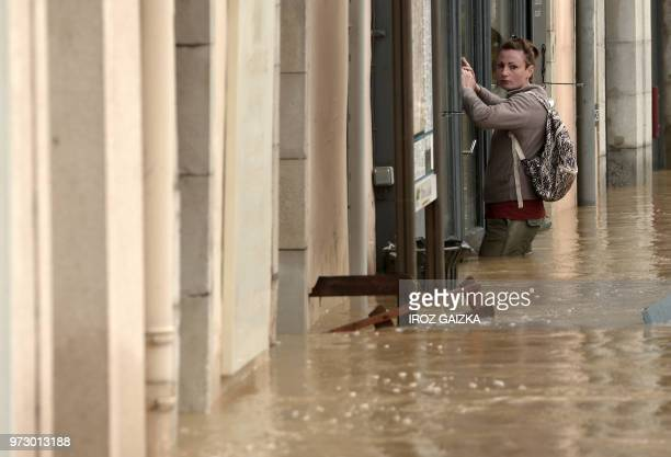 TOPSHOT A woman stands in thighhigh flood waters outside a shop window following heavy rains in SaliesdeBearn south western France on June 13 2018