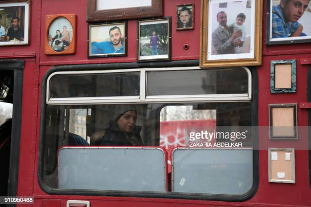 A woman stands inside a 'Freedom Bus' displaying portraits of people detained or missing after it was driven onto the Place de la Republique in Paris...