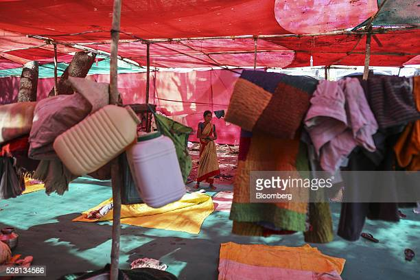 Woman stands inside a temporary suburban camp, set up by local political party Shiv Sena for the rural poor traveling to Mumbai to find water, in...