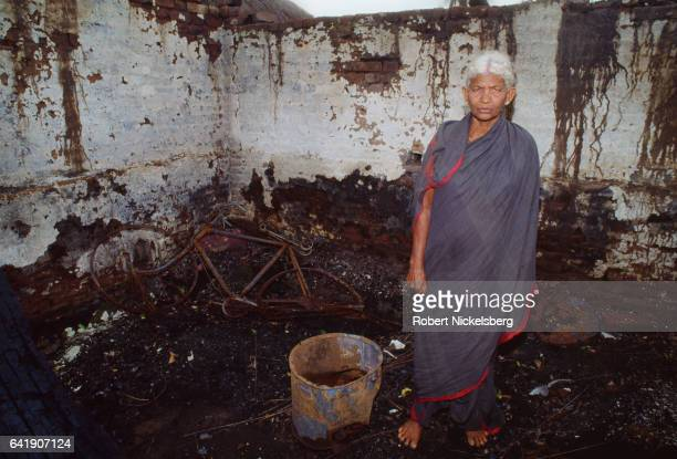 A woman stands inside her family's burned out home October 28 1991 in rural Andhra Pradesh India A number of families belonging to the Reddy caste...