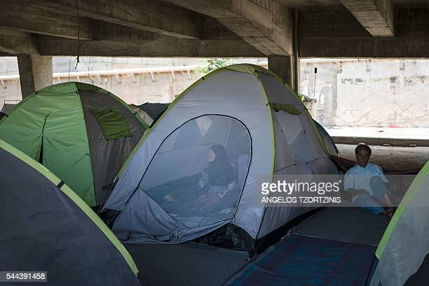 A woman stands inside her tent as a man sits on the ground beside her at the port of Piraeus where nearly 1500 refugees and migrants live at a...