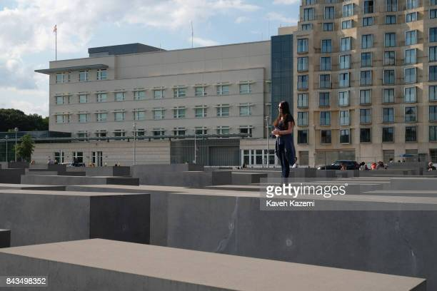 A woman stands lon a concrete slabs or 'stelae' in The Memorial to the Murdered Jews of Europe also known as the Holocaust Memorial designed by...