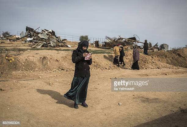 A woman stands looking at her mobile phone as people make their way to the funeral of Yakub alQian on January 24 2017 in UmelHiran Israel AlQian's...