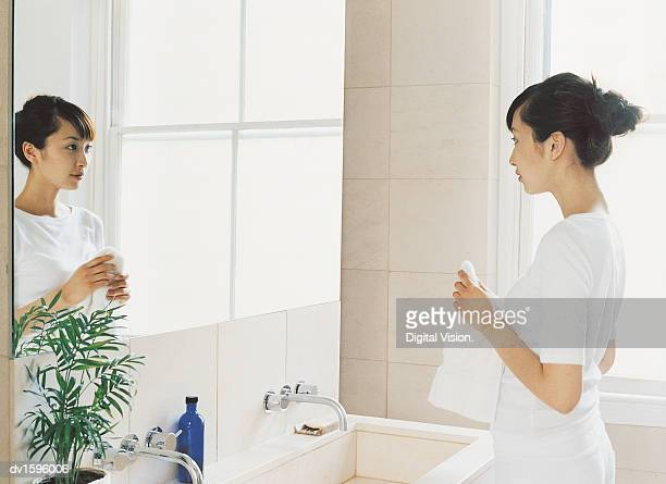 Woman Stands Looking at Herself in a Bathroom Mirror Holding a Towel
