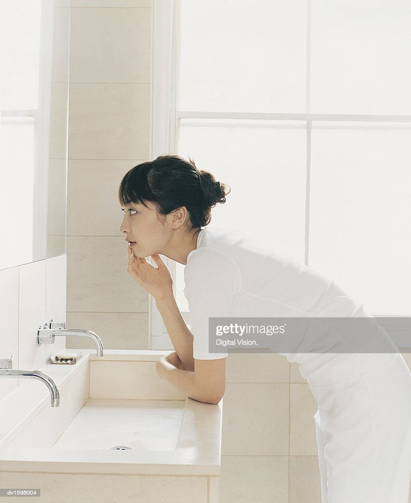 Woman Stands Looking at Herself in a Bathroom Mirror : Stock Photo