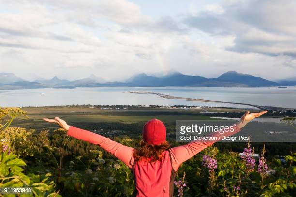 A Woman Stands Looking Out Over Homer Spit, Kachemak Bay And The Kenai Mountains With Arms Outstretched In Awe