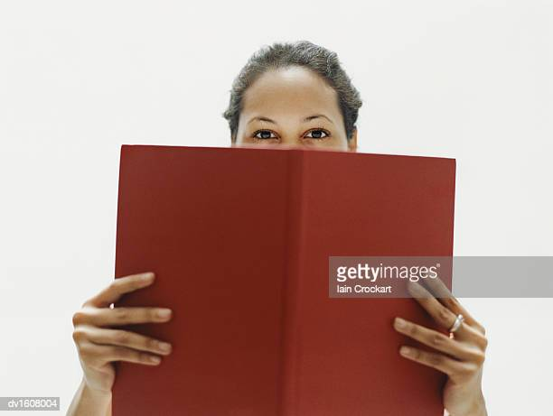 Woman Stands Looking Over a Red Book She is Holding