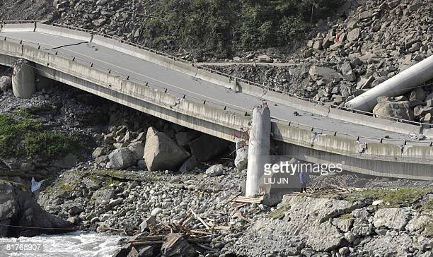 A woman stands near a collapsed bridge in one of the worst earthquakehit areas of Yingxiu town in Wenchuan county in China's southwestern province of...