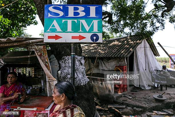 A woman stands near a signage indicating the direction to State Bank of India automated teller machines on the proposed site of the Andhra Pradesh...