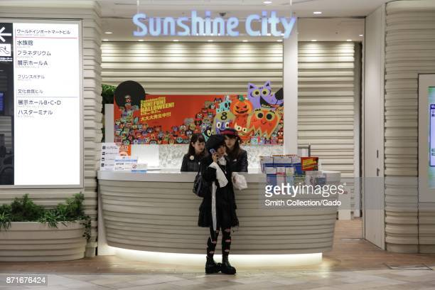 A woman stands near an information desk and makes a phone call inside Ikebukuro Sunshine City a shopping complex in the Ikebukuro ward Toshima Tokyo...