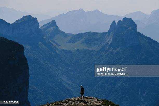 Woman stands near the Parmelan mountain refuge in Dingy-Saint-Clair, in the French Alps above Annecy, on August 11, 2021. - Mountain refuges are...