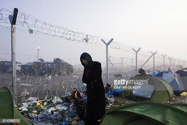 A woman stands next the razortopped fence marking the GreekMacedonian border near the Greek village of Idomeni on March 8 where thousands of refugees...
