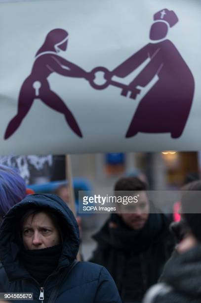 A woman stands next to a banner of a woman taking a key from a priest during a protest against the rejected civic proposal of law to liberalize...