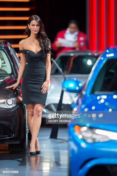 A woman stands next to a car at the Alpha Romeo booth at the 2018 North American International Auto Show in Detroit Michigan January 15 2018 The...
