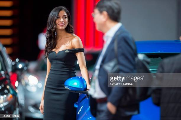 A woman stands next to a car at the Alpha Romeo booth at the Press Preview for the 2018 North American International Auto Show in Detroit Michigan...