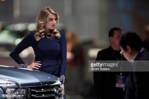 A woman stands next to a car at the GAC booth at the 2018 North American International Auto Show in Detroit Michigan January 15 2018 The Detroit Auto...